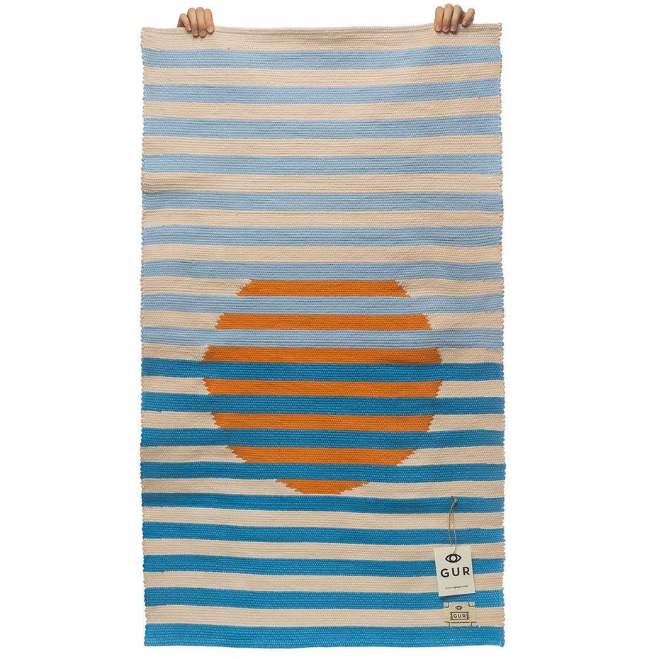 regalo número 3. una alfombra blanca con rayas celestes y azules y una bola naranja detrás de ellas, como una puesta de sol